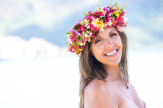 Beautiful woman wearing colorful flower crown while on a tropical island vacation in Bora Bora near Tahiti in French Polynesia
