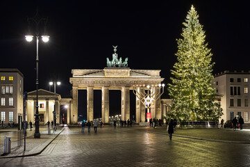 Berlin, Germany. Christmas tree and Hanukkah menorah at Pariser Platz (Paris' square) in front of Brandenburg Gate in night.