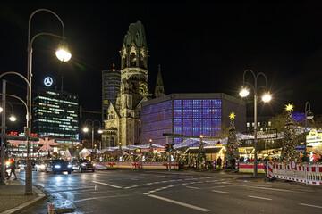 Berlin, Germany. Christmas market at Breitscheidplatz square around the Kaiser Wilhelm Memorial Church (mostly known as Gedachtniskirche) in night.