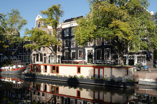 Houses and houseboat mirror in the water of the Prinsengracht right opposite the Anne Frank house in Amsterdam, early in the morning