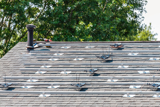 Rooftop installation work for solar panels racking with racks rails mounted on top of house residential home roof for off-grid living in Northern Virginia, USA with drill tool