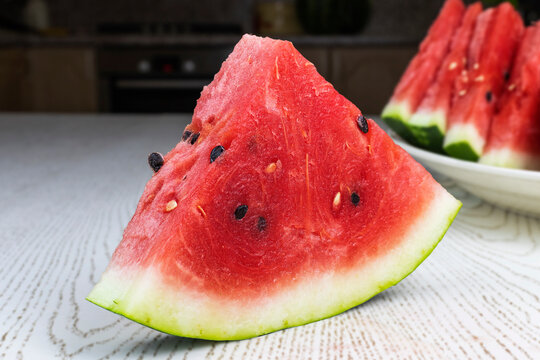 The sliced watermelon lies on an oval plate.