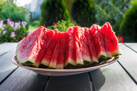Sliced juicy red watermelon on a platter on a garden table against a garden background