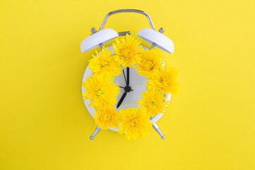 Yellow flowers on the dial of the white alarm clock in the center of the yellow surface