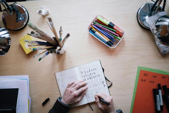 A designer sketching behind his desk at home