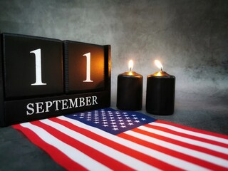 September 11th. Patriot Day and Memorial concept. Two burning candles with United States of America flag on dark background. Copy space.