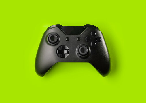 Black game controller isolated on green background