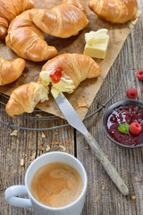 Rustikales Croissant-Frühstück mit Butter, Marmelade und einem Haferl Kaffee Crème - Breakfast with freshly baked croissants on a cooling rack, served with butter,  jam and a cup of coffee creme