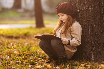 Cute little girl reading a book sitting under a tree in the park in autumn. Learning concept. Retro...