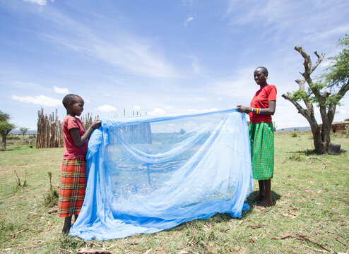 Mother and daughter preparing mosquito net for the daughter's sleeping area.