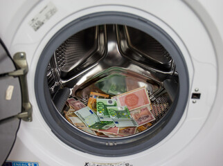 A pile of dirty money in a clothes machine. washing steam in the drum of the washing machine