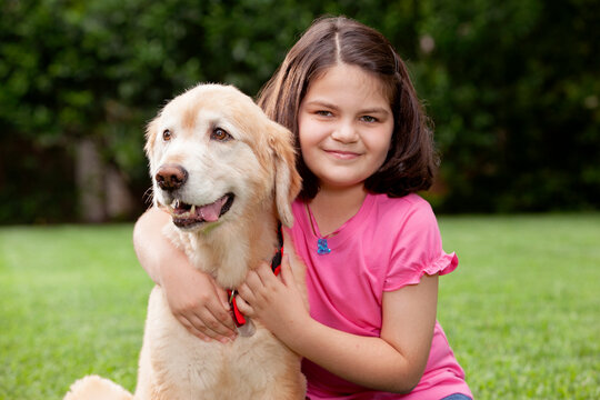 Portrait of young girl and her young golden retriever in backyard