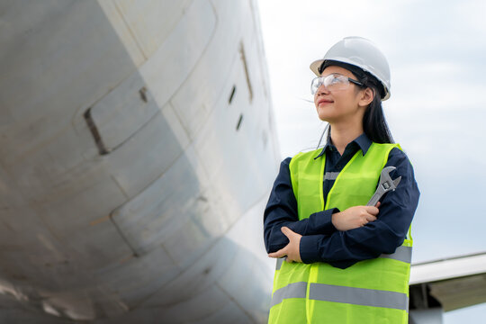 Asian woman engineer maintenance airplane arm crossed and holding wrench in front airplane from repairs, fixes, modernization and renovation in airport..