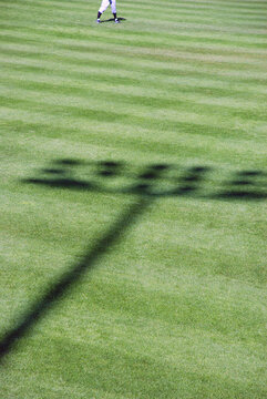 Shadow of baseball stadium lights on field with outfielder