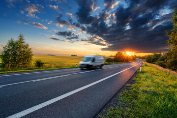 Fotobehang - Motion blurred white fast delivery van driving on the asphalt road in rural landscape in the rays of the sunset with dark storm cloud