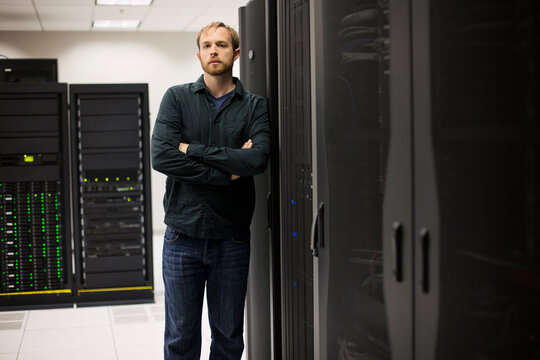 Young IT engineer standing near datacenter servers