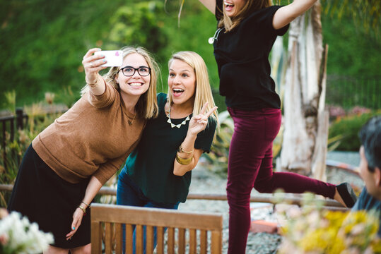 Two young women take a selfie as the third photo bombs their picture.