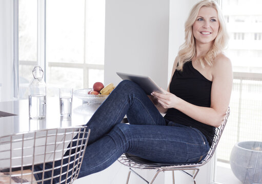 Smiling woman with a tablet PC at a kitchen breakfast bar.