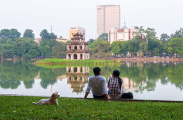 Friends talking along the Hoan Kiem lake with the turtle pagoda and modern buildings in the background in Hanoi, Vietnam. Wall mural