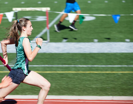 Teenage girl in first place at a track meet in the 4x100 relay