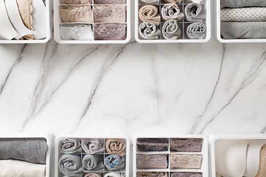 Womans underwear, pajamas and socks neatly folded and placed in closet organizer drawer divider on white marble table.