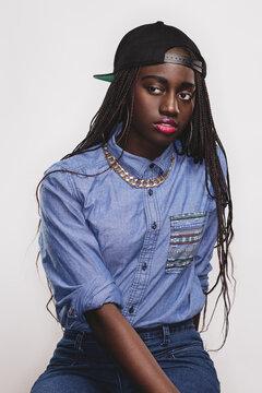 A pretty black girl with braids and a backward baseball cap