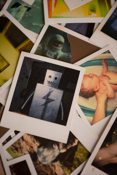 Instant photos in a pile including one of a robot costume and one of a newborn baby getting a bath.