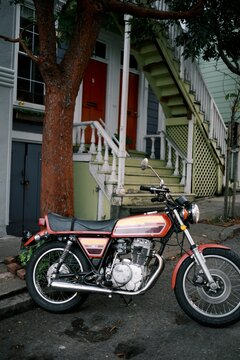Old small 350 motorcycle sitting on an urban city street.