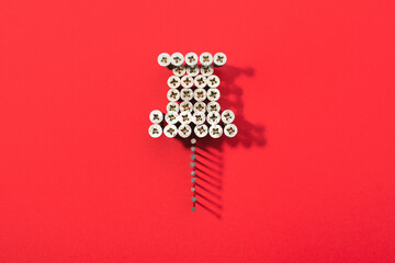 A pin shaped with lot of screws on red background. Social media icon.