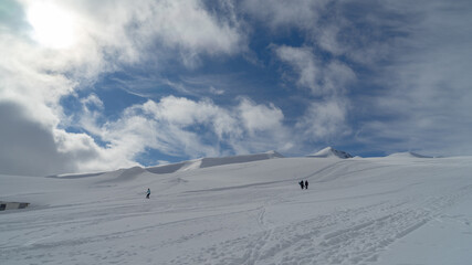The image of snowboarders on a snowy mountain top.