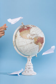 World globe with paper airplanes flying around