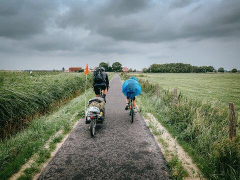 Vater und Sohn radeln bei windigem Wetter nebeneinander in Richtung Horizont, Ostfriesland