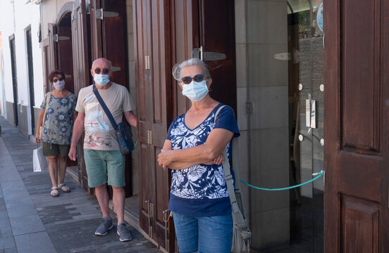 Three mature people standing in the street maintaining social distancing and wearing surgical mask as new normality waiting to enter in a restaurant or shop