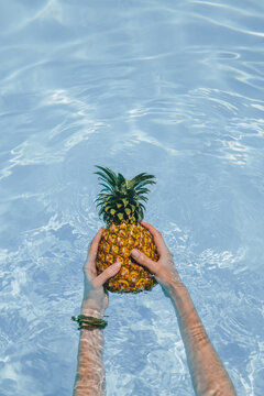 Hands holding pineapple in a pool