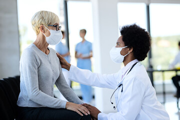 Black doctor and mature patient wearing protective face masks while talking in waiting room at...