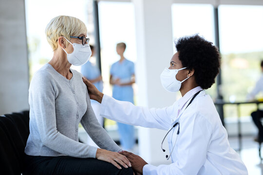 Black doctor and mature patient wearing protective face masks while talking in waiting room at clinic.