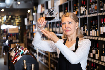 Portrait of middle aged woman professional sommelier tasting natural wines in winery ..