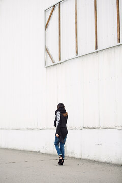 Outfit inspiration - blogger walking away in front of a white wall