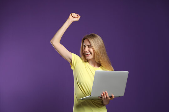 Portrait of emotional woman with modern laptop on purple background