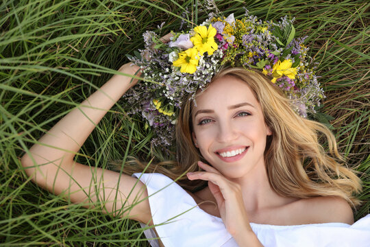 Young woman wearing wreath made of beautiful flowers on green grass, top view