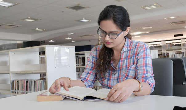 Photo of beautiful and intelligent young girl with eyeglasses studying hard in public library for upcoming exams. Every college going student may connect to this picture for various scenarios.