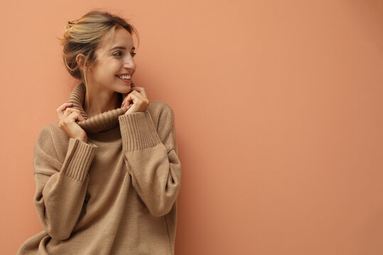 Beautiful young woman wearing knitted sweater on light brown background. Space for text