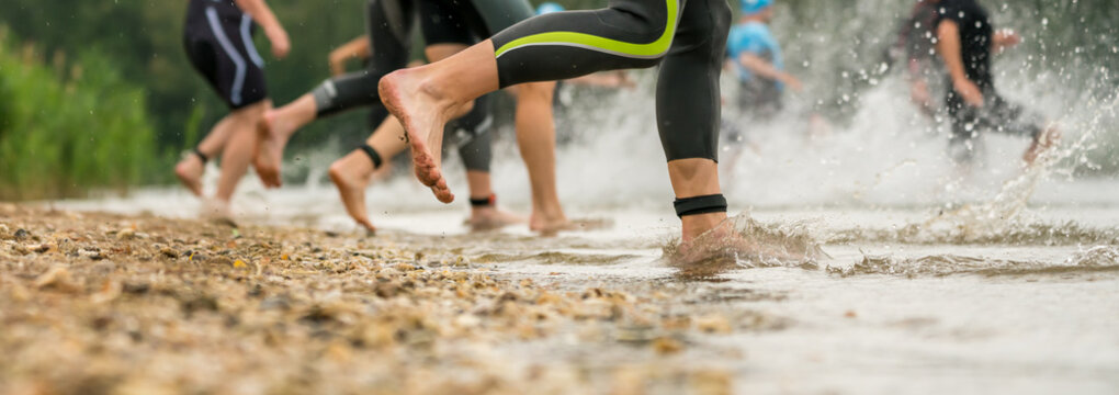 Athletes in wetsuits running into a lake at a triathlon competition