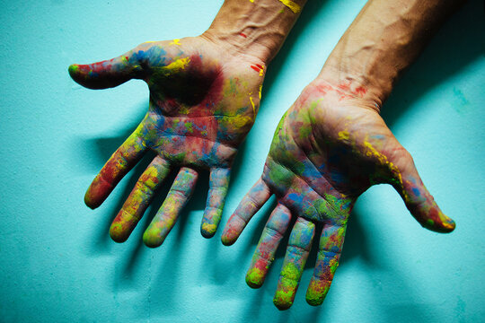Colourful painted male hands in front of a blue wall