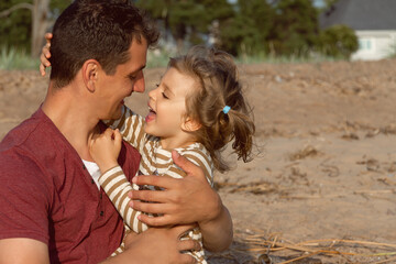 little happy daughter and father laugh and look at each other on beach