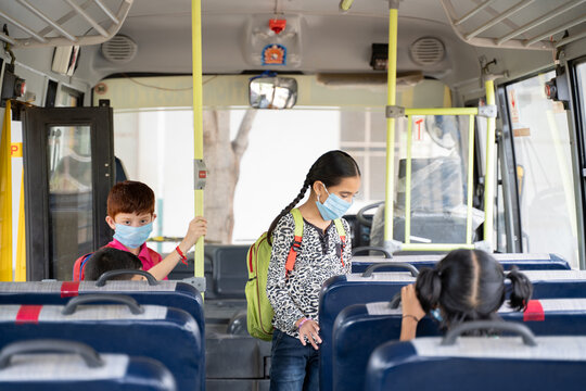 Kids with medical mask coming inside school bus and sitting on seats while maintaining social distance due to coronavirus or covid-19 pandemic - Concept of school reopen or back to school