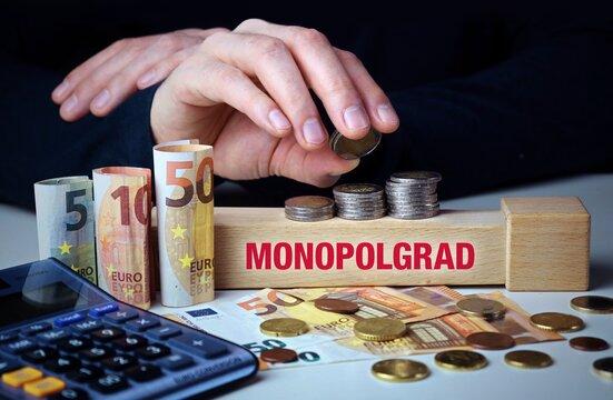 Monopolgrad. Hand baut Geldstapel auf einem Baustein mit Text. Turm aus Euro Münzen. Taschenrechner daneben.