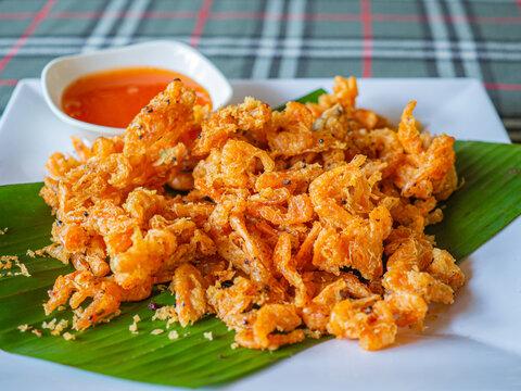 Crispy fried shrimp on a banana leaf on a white plate