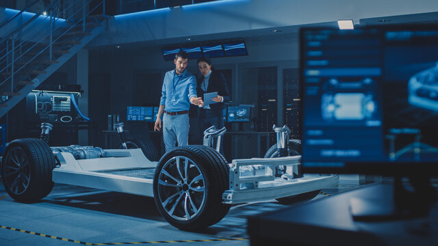 Auto Industry Design Facility: Male Chief Engineer Shows Car Prototype to Female Car Designer. Electric Vehicle Platform Chassis Concept with Wheels, Engine and Battery.