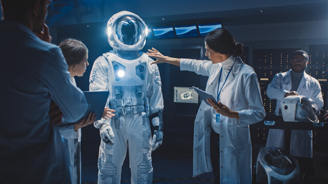 Diverse Team of Aerospace Scientists and Engineers Wearing White Coats have Discussion, Use Computers Design New Space Suit Adapted for Galaxy Exploration and Travel. Constructing Astronaut Suit